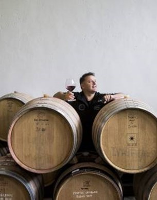 Andy Anderson standing behind wine barrels