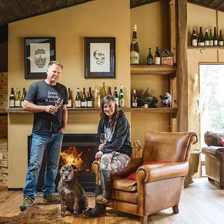 Duncan Forsyth and Anna Riederer infront of a fireplace with a dog