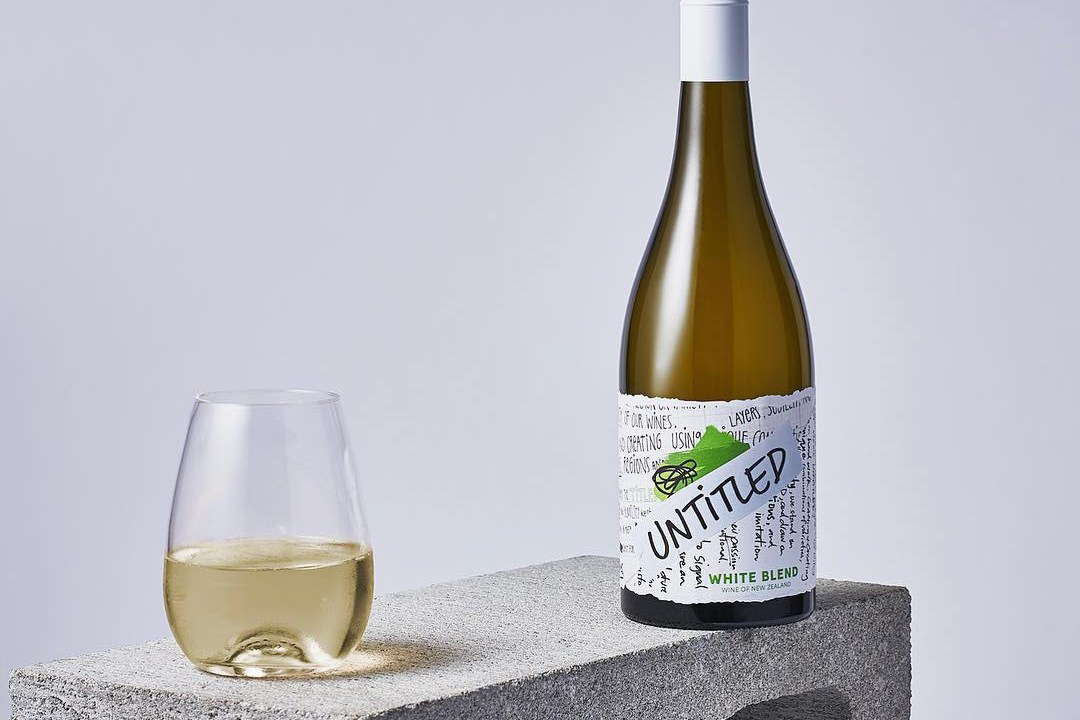A wine bottle of Untitled Wines' white blend next to a filled glass