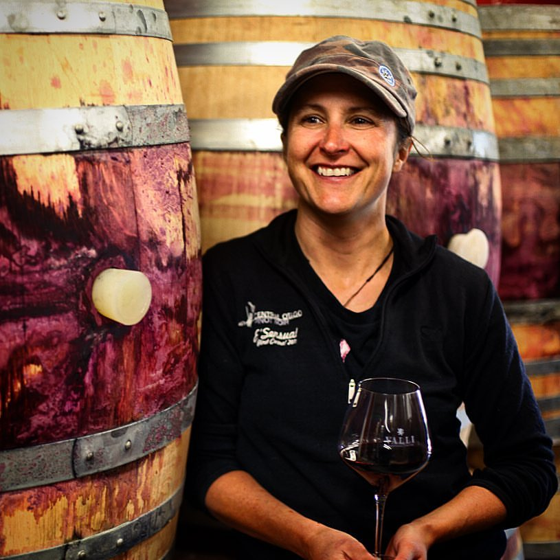 Jen Parr holding a glass of red wine next to barrels