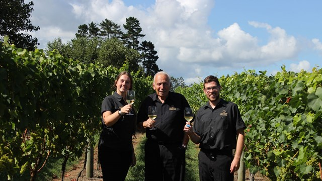 The Soljians holding glasses of white wine in a vineyard