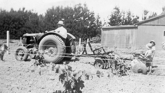 Man on a tractor with two children beside