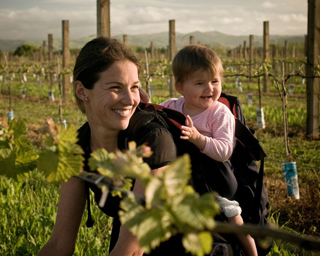 Kirsten Searle planting vines with a baby on her back