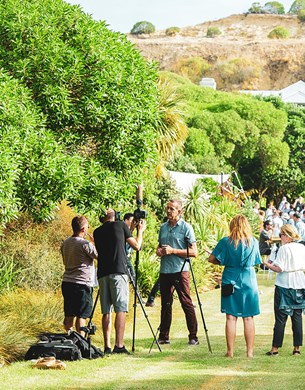 A media group interveiwing people infront of a crowd at a vineyard.