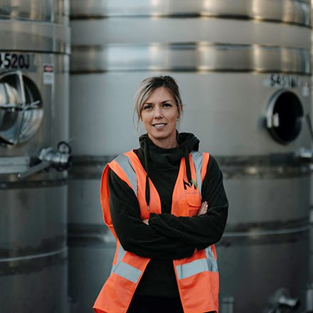 Alice Rule standing infront of tanks in a winery