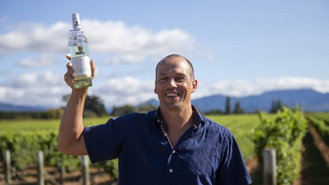Man in vineyard holding up a bottle of wine