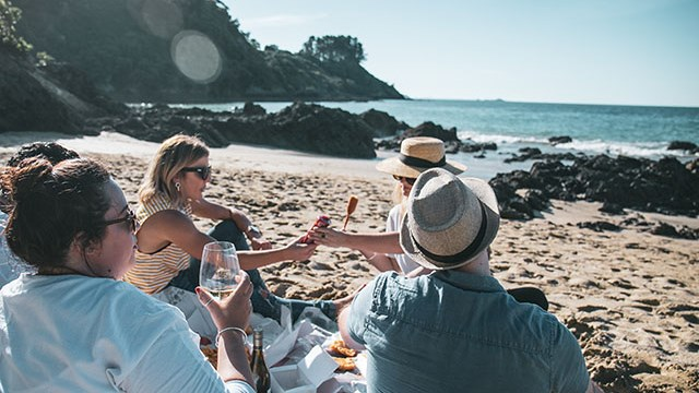 People on beach with glass of sauvignon blanc